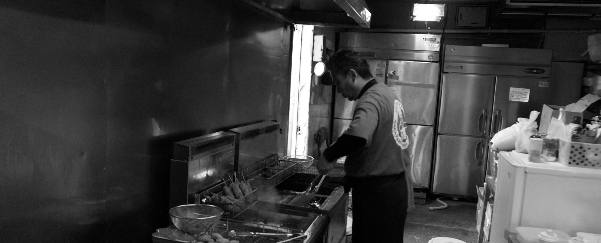 からあげ まんぷく亭の店主國友聖一が、岩出市の店舗でこだわりのからあげを調理している